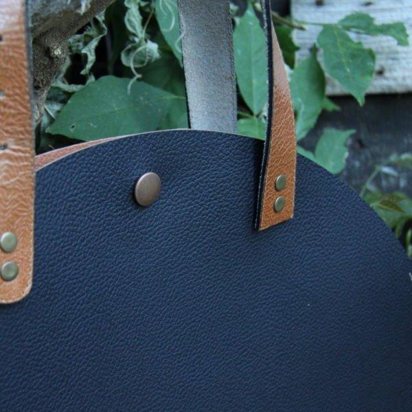 Sac rond en simili noir anses en croûte de cuir marron