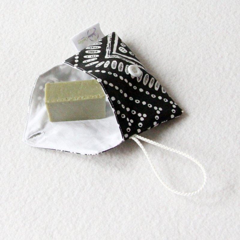 Pochette imperméable à savon ou shampoing solide zéro déchet en tissu enduit noir et blanc avec bouton blanc
