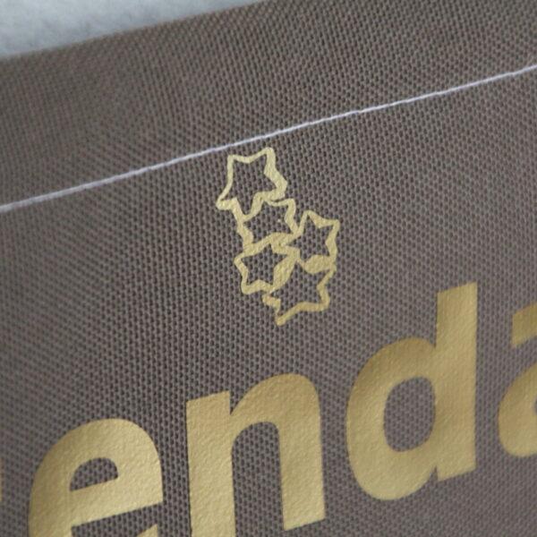 Calendrier de l'avent en tissu fond taupe et poches blanches avec des étoiles dorées