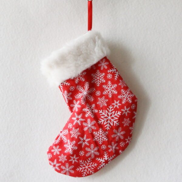 Chaussette de Noël rouge avec des flocons blancs et haut de la chaussette en fourrure blanche